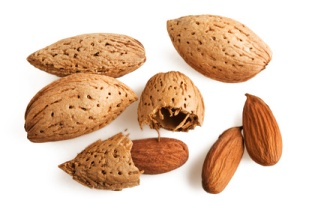 almonds in their shell and cracked open and outside of their shell for skin and health benefits