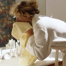 woman washing face and drying with towel