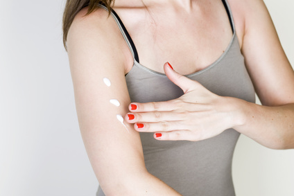 woman applying sunscreen lotion on arm to prevent premature skin aging