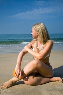 woman applying suntan lotion on her skin as a skin cancer prevention method